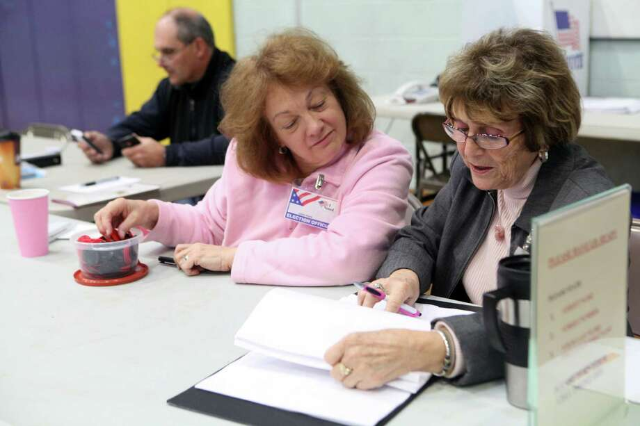 Checkers, Carol Pisani, left, and Rosemarie Fedorko, assist voters at Hillcrest Middle School in Trumbull, Conn. on Tuesday, Nov. 5, 2013. Photo: BK Angeletti, B.K. Angeletti / Connecticut Post freelance B.K. Angeletti