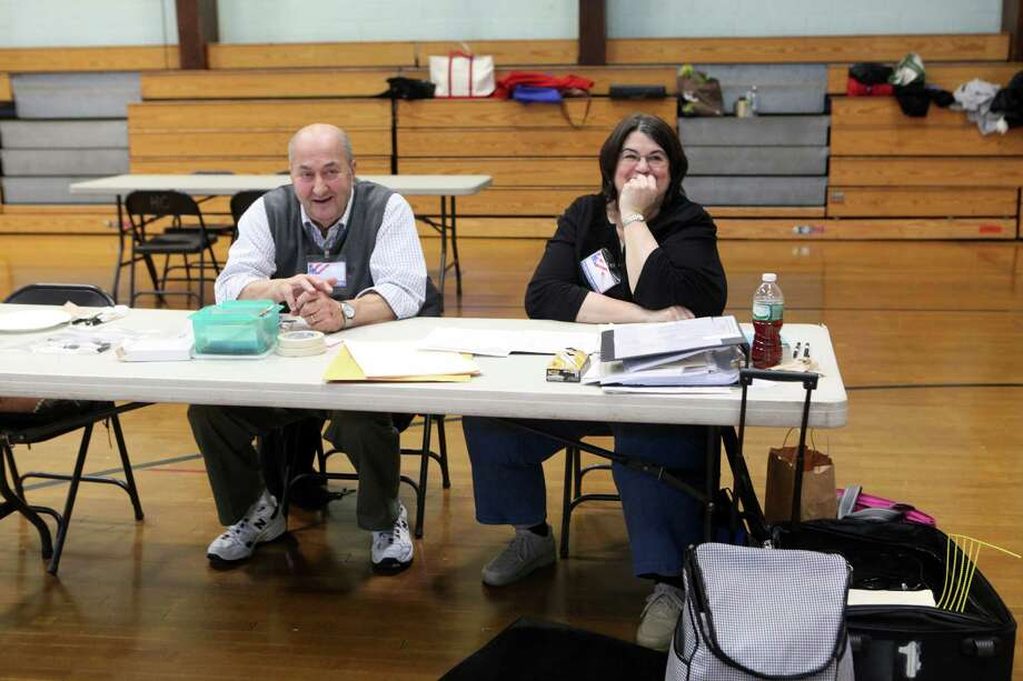 Ralph Monaco, left, and Moderator Jackie Ditulio assist voters at Hillcrest Middle School in Trumbull, Conn. on Tuesday, Nov. 5, 2013. Photo: BK Angeletti, B.K. Angeletti / Connecticut Post freelance B.K. Angeletti