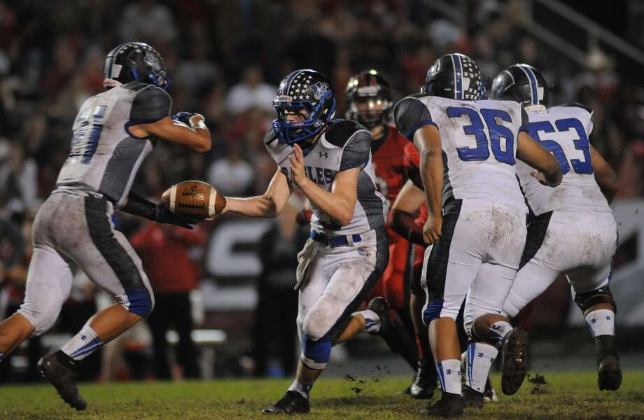 New Caney quarterback Cody Young, right, handed the ball to running back Jordan Alexander, left, during the Eagles' win over Porter. Young completed 9 of 18 passes for 142 yards in the game. Photo: Jerry Baker, Freelance
