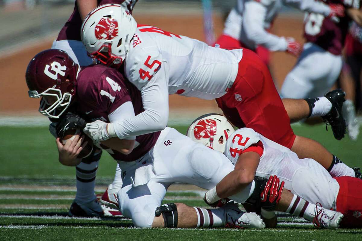 Cinco Ranch quarterback Luke Klingler (14) was sacked by Katy linebackers Jake Blomstrom (45) and Paddy Fisher (42) during Saturday's game.