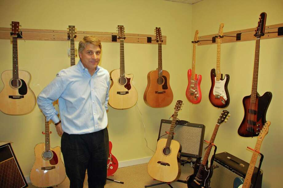 New Canaan Music owner Phil Williams displays some of the newly arrived Martin guitars available in his shop at 72 Park St. Jarret Liotta/For the New Canaan News Photo: Contributed / New Canaan News Contributed