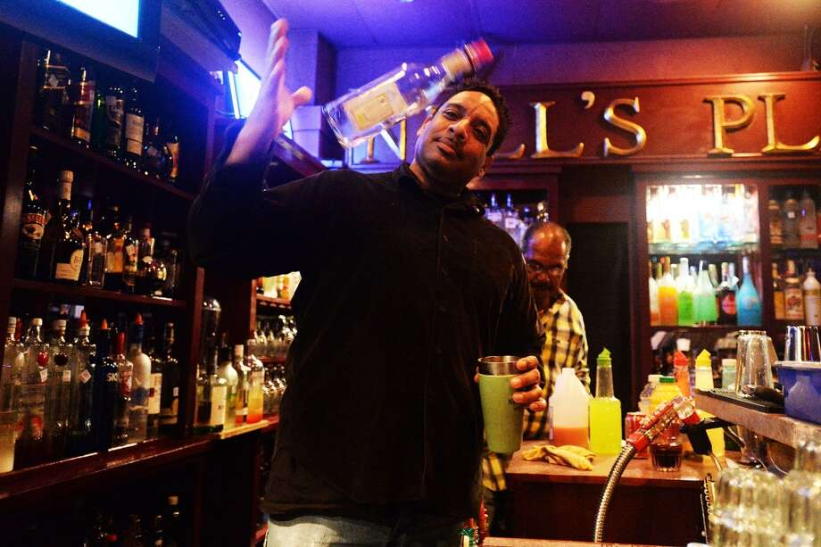 John Duplechain prepares a mixed drink while bar tending at Nell's place Wednesday karaoke night. Michael Rivera/The Enterprise