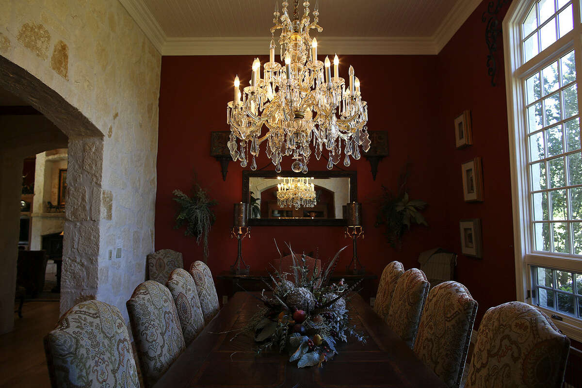 A crystal chandelier offers textural contrast with limestone walls in the dining room.