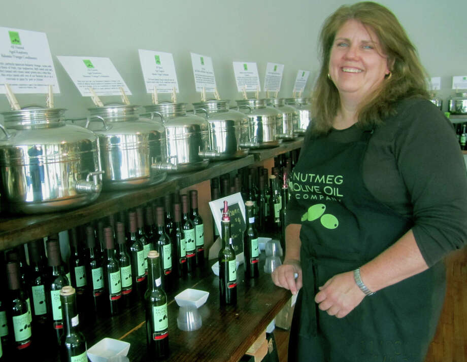 Maureen Kenny offers a welcoming smile to patrons of her Nutmeg Olive Oil Company shop along Main Street in New Milford. November 2013 Photo: Norm Cummings / The News-Times