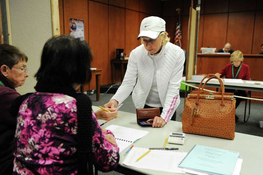 Susan Ness shows her ID to vote at Town Hall in Greenwich, Conn. on Tuesday November 5, 2013. Photo: Dru Nadler / Stamford Advocate Freelance