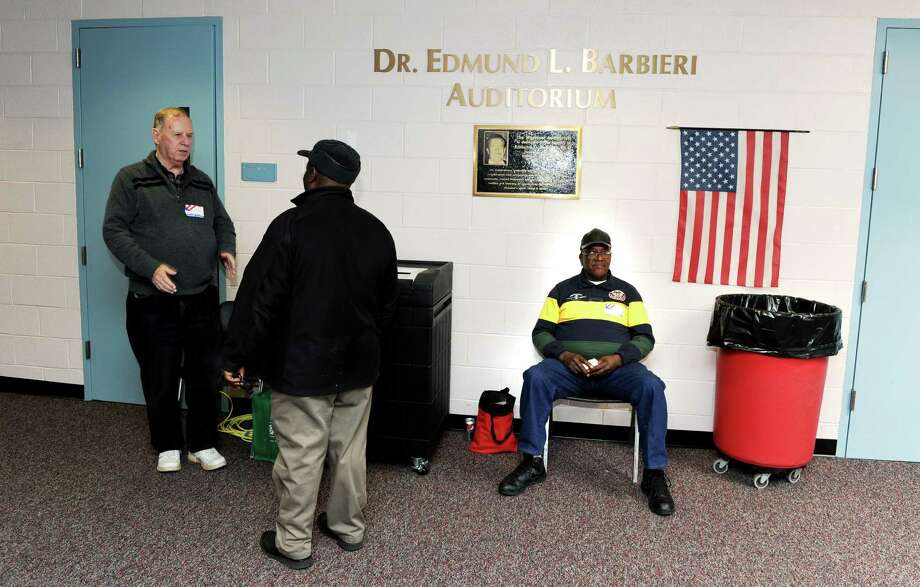 Volunteers John Newton and Harold McAllister help Sony Jean-Louis ( center) cast his ballot at Westover School in Stamford, Conn. on Tuesday November 5, 2013. Photo: Dru Nadler / Stamford Advocate Freelance