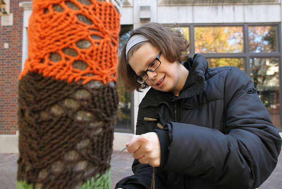 Born to knit:Iowa winters are so cold that the citizens of Iowa City crochet stockings for their trees. Here Sara Miller stitches a lovely trunk warmer on a downtown street. Photo: Benjamin Roberts, Associated Press