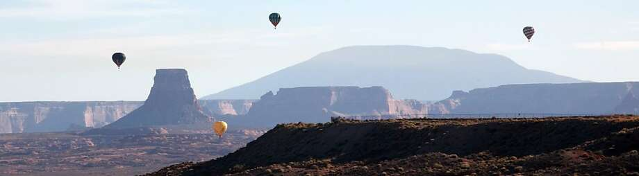 Early risers: Hot-air balloons drift east by Tower Butte and Navajo Mountain on a clear morning in Page, Ariz. Photo: Jud Burkett, Associated Press