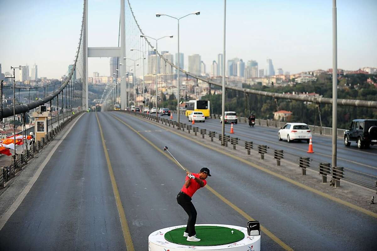 One heck of a par 5: Tiger Woods attempts to hit a ball from Asia to Europe as he tees off on the Bosphorus Bridge in Istanbul. Woods is in Turkey to attend the Turkish Airlines Open in Antalya.