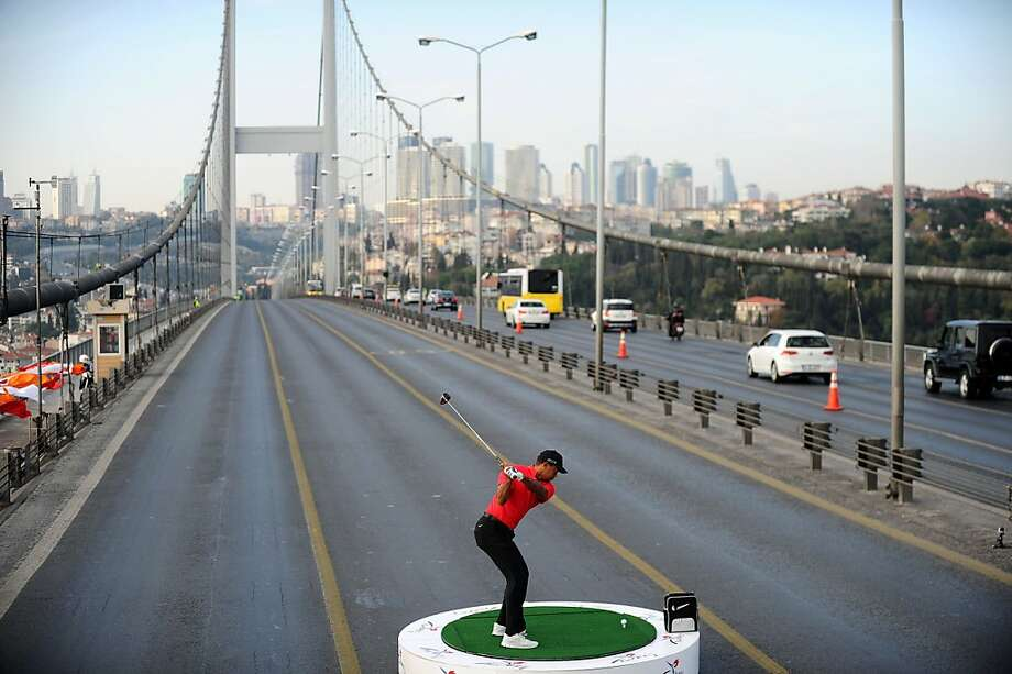 One heck of a par 5:Tiger Woods attempts to hit a ball from Asia to Europe as he tees off on the Bosphorus Bridge in Istanbul. Woods is in Turkey to attend the Turkish Airlines Open in Antalya. Photo: Bulent Kilic, AFP/Getty Images