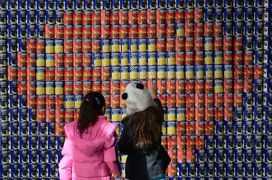 "Souperman:Schoolchildren look at a Superman logo made entirely out of food cans at the ""Canstruction"" exhibition and food drive in New York. The canned goods will be donated to City Harvest and distributed to some 400 soup kitchens and food pantries throughout the city. Photo: Emmanuel Dunand, AFP/Getty Images"