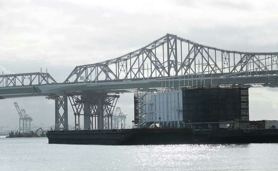 This photo shows a barge on Treasure Island with the eastern span of the San Francisco-Oakland Bay Bridge at rear in San Francisco, Tuesday, Oct. 29, 2013.  The barge is one of three mysterious floating structures that have sparked online speculation. The secretive structures, two in San Francisco and one Portland, Maine, are registered with a Delaware corporation as BAL0001, BAL0010, BAL0011 and BAL0100. (AP Photo/Jeff Chiu) Photo: Jeff Chiu, Associated Press / Associated Press