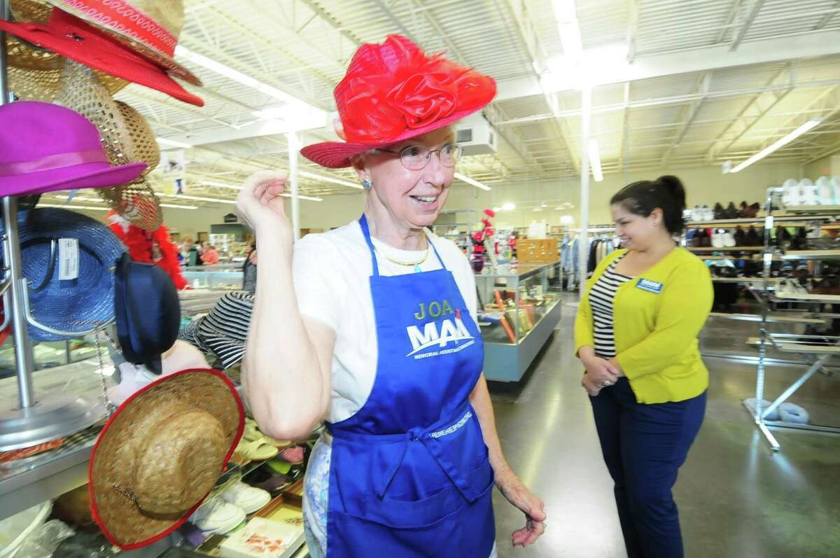 Joan Giese, who has volunteered for 30 years with Memorial Assistance Ministries, tries on one of the hats available at the ministries' thrift shop as Veronica Garcia looks over merchandise for sale.