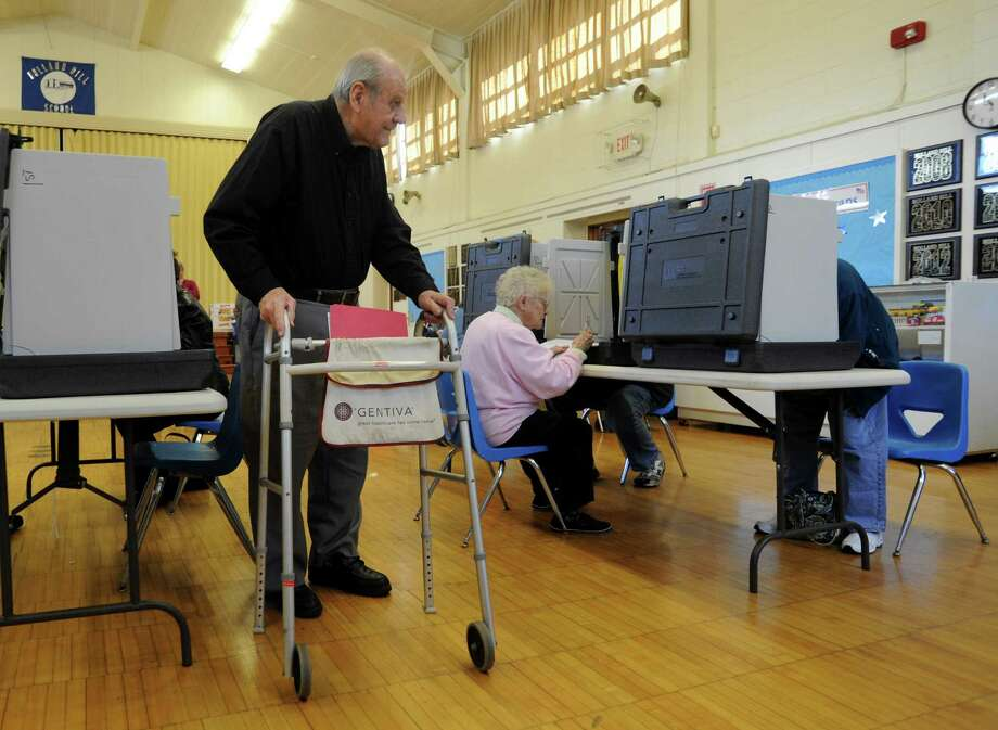 Richard Purchase heads to the ballot box while is wife Dorothy Purchase, right, still works on her ballot at Holland Hill School in Fairfield, Conn. on Tuesday, Nov. 5, 2013. Photo: Cathy Zuraw / Connecticut Post