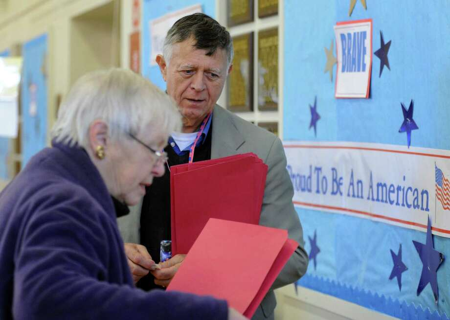 Tab Tender, Harvey Martin, assists a voter at Holland Hill School in Fairfield, Conn. on Tuesday, Nov. 5, 2013. There was steady steam of voters coming in to cast their ballots. Photo: Cathy Zuraw / Connecticut Post