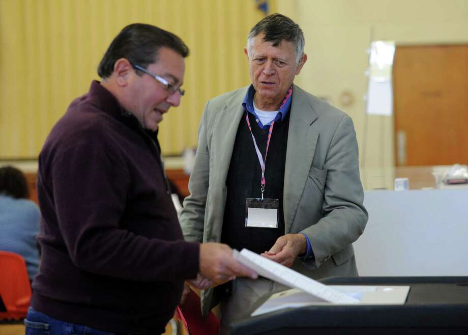 Harvey Martin, the tab tender at Holland Hill School in Fairfield, Conn. assists resident Tony Rando cast his ballot on Tuesday, Nov. 5, 2013. Photo: Cathy Zuraw / Connecticut Post