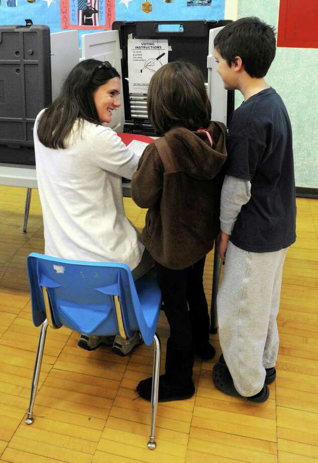 "Sarah Heath takes avdantage of a ""teachable moment"" and shows her children, Tatum and Camden Cocker how to vote. A steady steam of voters cast their ballot at Holland Hill School in Fairfield, Conn. on Tuesday, Nov. 5, 2013. Photo: Cathy Zuraw / Connecticut Post"