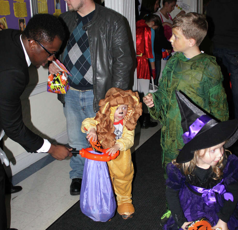 A student staff Ayoade Adeyemi giving out  candies to a Starlight Child's sibling Chase Fitzgerald, 2 and a half   Photo by Karen Fitzgerald