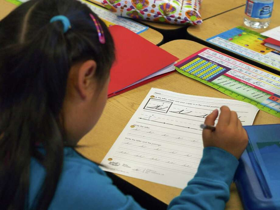 TO GO WITH AFP STORY by Rob MacPherson, Lifestyle-education-US-writing A pupil practices cursive writing at Triadelphia Ridge Elementary School in Ellicott City, Maryland on October 15, 2013. For third-grade pupils at Triadelphia Ridge Elementary School, learning to write joined-up letters is a no-brainer, but outside the classroom, grown-up Americans are debating whether the nation's children should be studying cursive at all.   AFP PHOTO / Robert MacPhersonRobert MacPherson/AFP/Getty Images Photo: ROBERT MACPHERSON / AFP