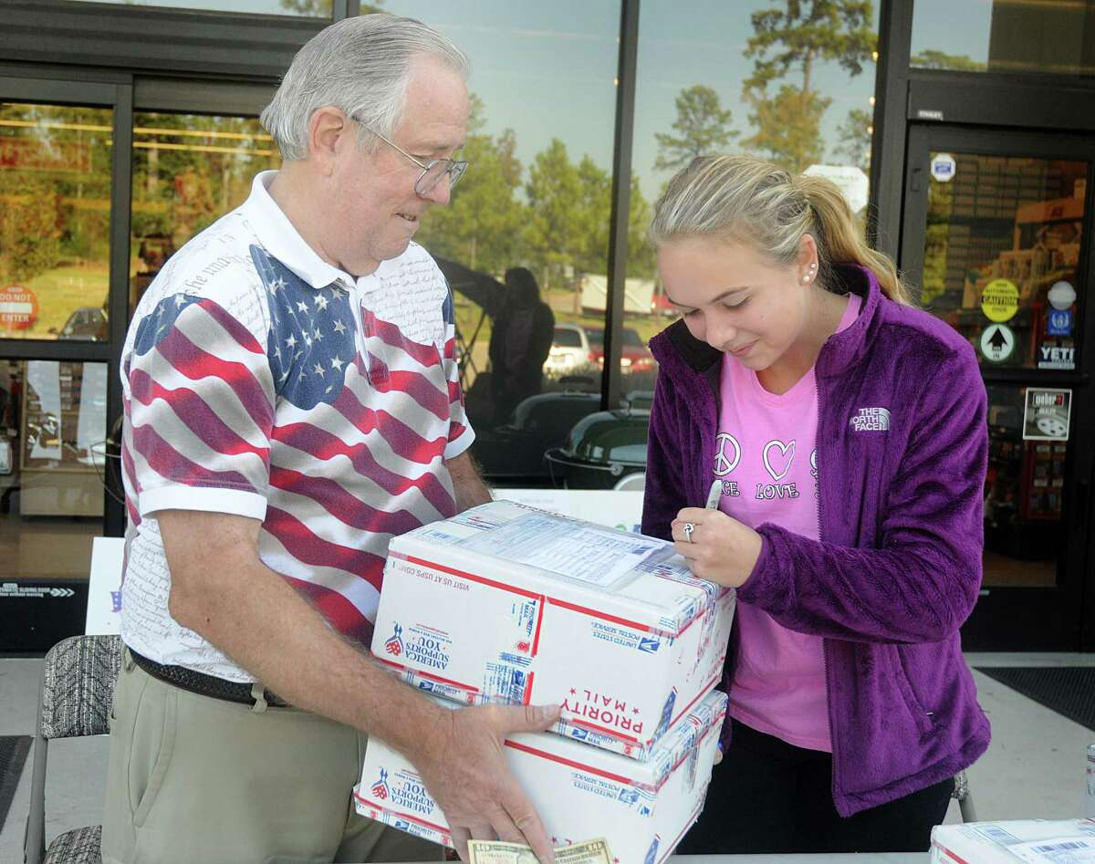 Dennis Bernhart, of The Woodlands chapter of Cypress Cares, and National Charity League Laurel Chapter volunteer Madi Bruddage draws a smiley face on a care package for troops in Afghanistan.