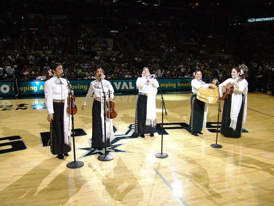 Mariachi Mujer Internacional performs at a Spurs game. The group's white-accented outfits are something they wear only for the Spurs and have become their signature fashion statement. Photo: Courtesy Lucila Diaz