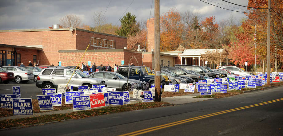 Campaign signs line the sidewalk outside Orange Avenue School in Milford as candidates greet voters on Tuesday, November 5, 2013. Photo: Brian A. Pounds / Connecticut Post