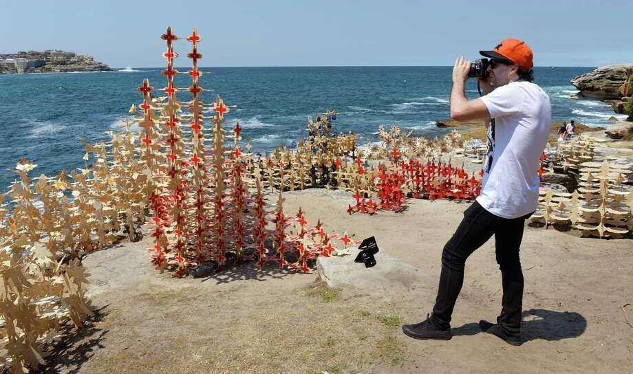 A man takes a photo of a sculpture by the Coral Collective titled 'Coral' and which is part of the Sculpture by the Sea exhibition which runs on the Bondi to Tamarama coastal walk in Sydney, on October 25, 2013.  The world's largest annual free-to-the-public outdoor sculpture exhibition runs 24 October - 10 November 2013 and features over 100 sculptures by artists from Australia and around the world. Photo: WILLIAM WEST, Getty Images / 2013 AFP