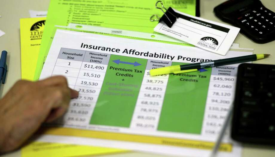 A volunteer uses a chart to help explain health insurance options. Under Obamacare, some people might qualify for subsidies to bring down the cost of premiums for a good plan. Photo: Eric Gay / Associated Press