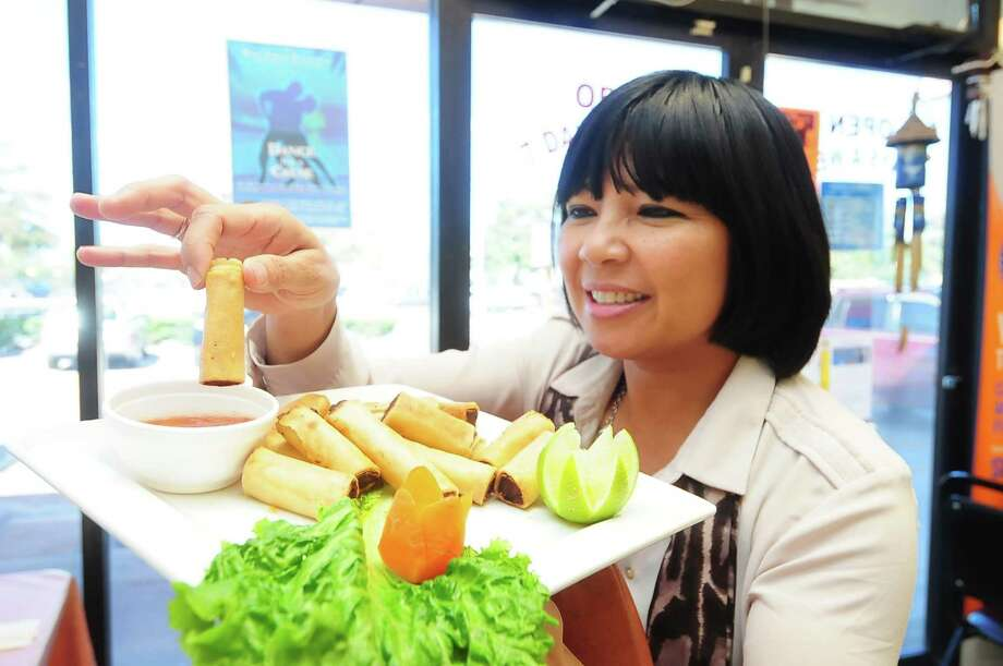 Asia Society marketing representative Tina Zulu samples the Lumpia Shanghai dish from Best of Filipiniana restaurant, which will be one of the vendors at Asia Society Texas Center's Night Market. Photo: Â Tony Bullard 2013, Freelance Photographer / © Tony Bullard & the Houston Chronicle