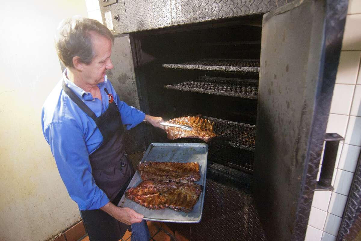 Frank Roche pulls a tray of ribs out of the pit.