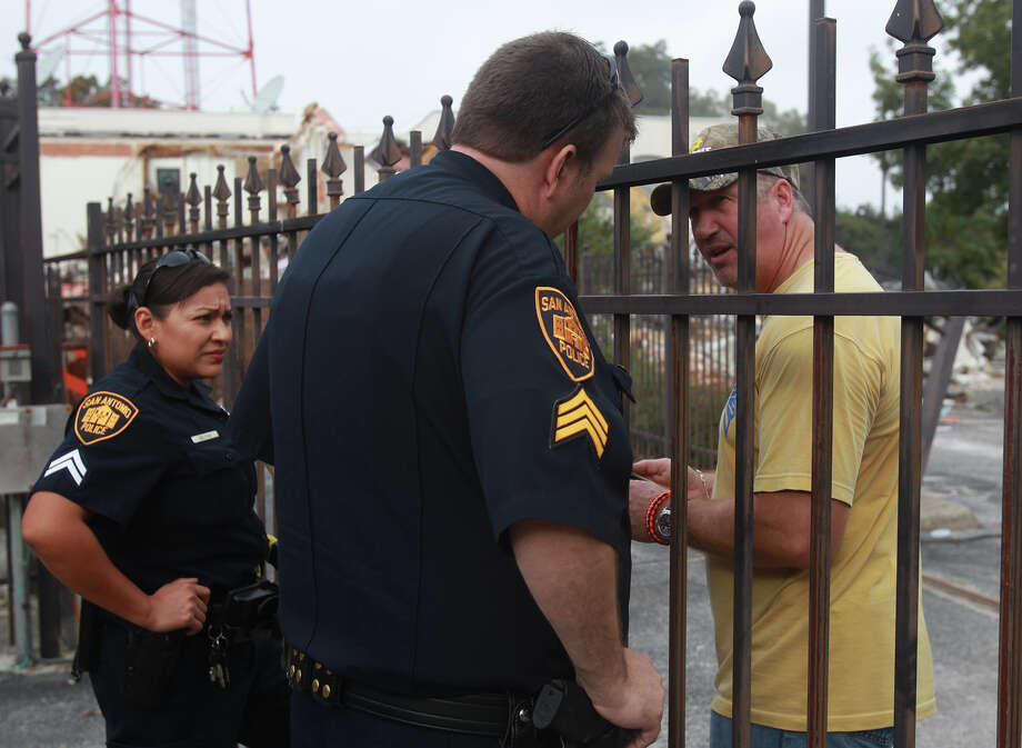 San Antonio police speak Tusaday November 5, 2013 with worker about a court order obtained to halt demolition of the Univision television building on Cesar Chavez Boulevard. Photo: JOHN DAVENPORT, SAN ANTONIO EXPRESS-NEWS / ©San Antonio Express-News/Photo may be sold to the public