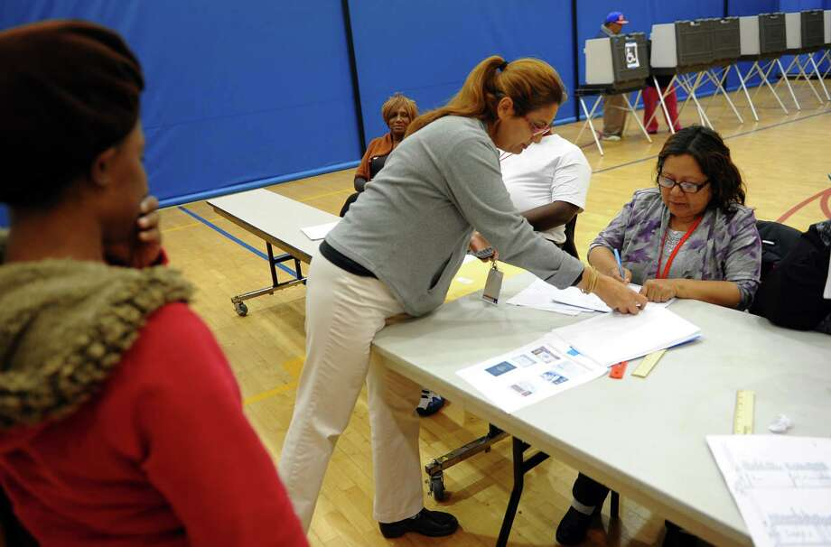 Moderator Julie Diaz, center, checks a voter's ID during Election Day at Cesar A. Batalla School in Bridgeport, Conn. on Tuesday November 5, 2013. Photo: Christian Abraham / Connecticut Post