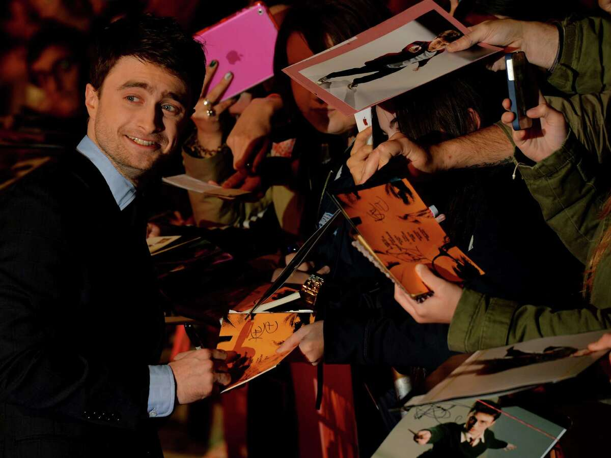 British actor Daniel Radcliffe signs autographs as he arrives for the premiere of