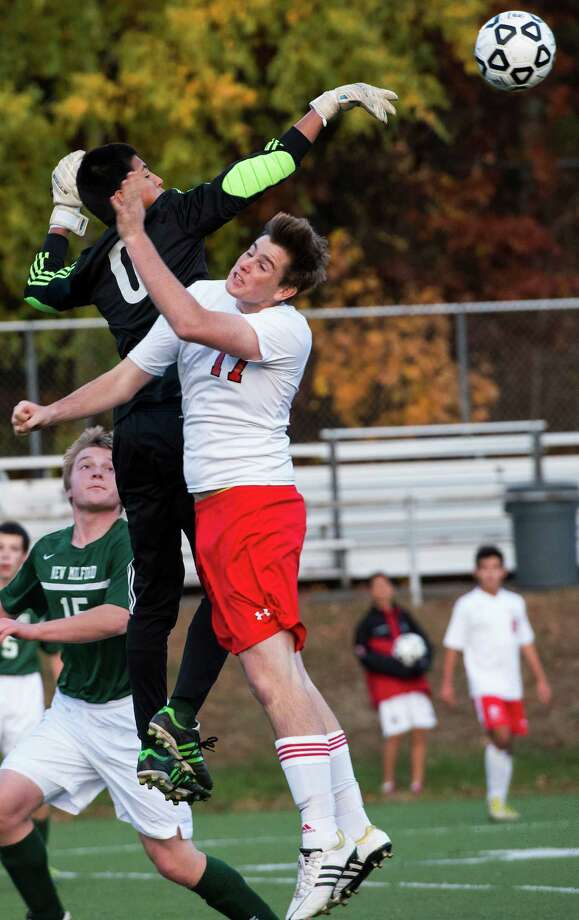 Fairfield Prep's Christian Backe runs into New Milford high school goalie Adam Llerena in front of the New Milford goal during the first round of the CIAC class LL boys soccer tournament played at Fairfield University, Fairfield, CT on Tuesday, November, 5th, 2013. Photo: Mark Conrad / Connecticut Post Freelance