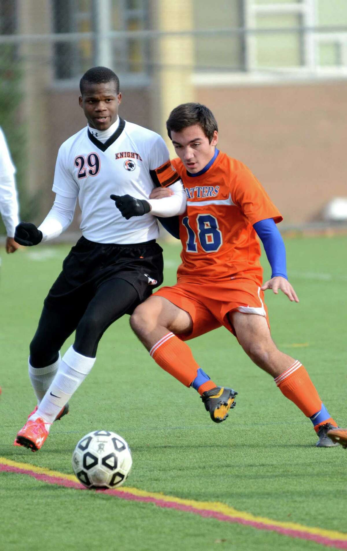 Stamford's Marc Guirand (29) and Danbury's Matthew Alvarez (18) battle for control of the ball during the Class LL boys soccer game at Stamford High School on Tuesday, Nov. 5, 2013.
