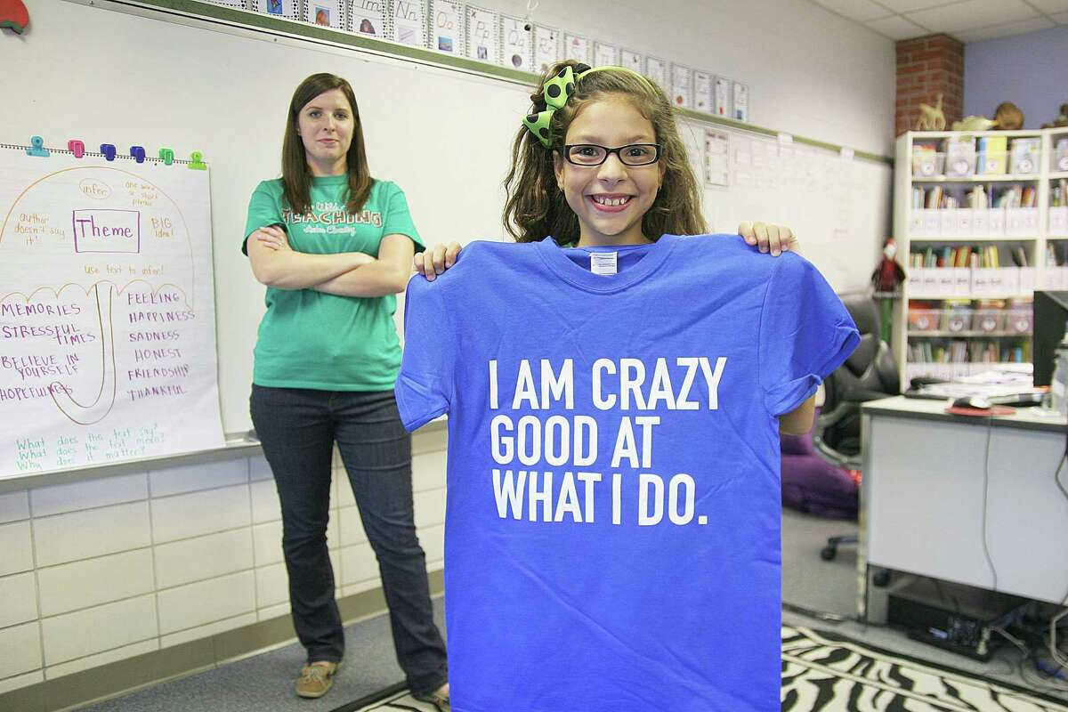 Fourth-grade teacher Katie Strong meets with Mia Quiroga, 10, to help set her academic goals. Students who complete their goals with The Grit Initiative will receive a free T-shirt.