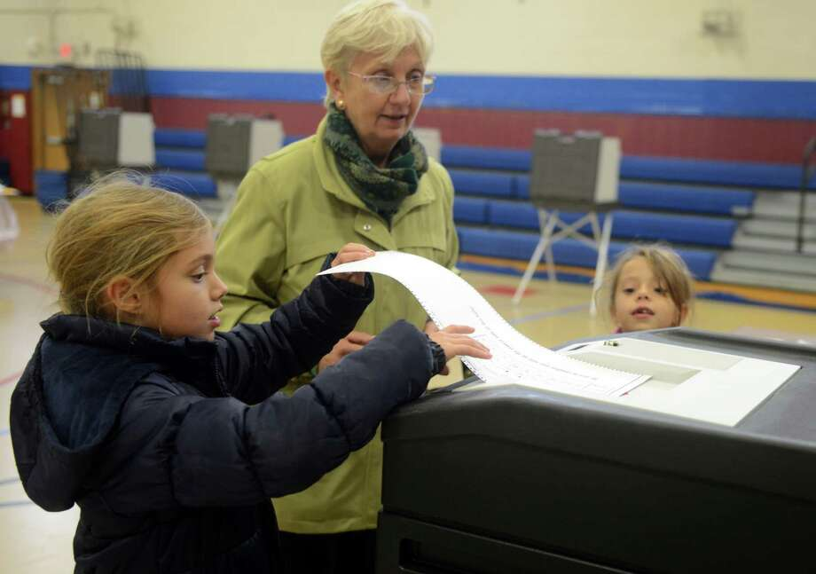 Cornelia Tarnoski gets some help casting her vote from granddaughters Anais Salageanu, 8, left, and  Adriana Salageanu, 6, at Irving School in Derby, Conn. Tuesday, Nov. 5, 2013. Photo: Autumn Driscoll / Connecticut Post