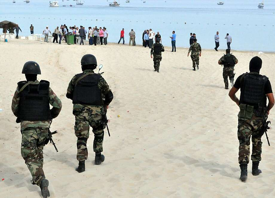 "Tunisian security forces inspect a beach after a failed suicide bomb attack near the four-star Riadh Palms hotel, in the resort town of Sousse, a popular tourist destination 140 kilometres (90 miles) south of Tunis, on October 30, 2013.  Tunisian security forces arrested five Salafist ""terrorists"" with links to two failed attacks in coastal resort towns, the first suicide bids in the country for more than a decade. Today's failed suicide bombings are the first in Tunisia since 2002, when an attack claimed by Al-Qaeda killed 21 people at the ancient Ghriba synagogue on the resort island of Djerba.  AFP PHOTO/STRSTR/AFP/Getty Images Photo: Str, AFP/Getty Images"