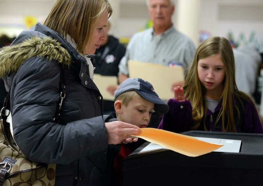 Kaitlyn Lariviere, 11, waves goodbye to the ballot as her mom Alisa casts her vote at John G. Prendergast School in Ansonia, Conn. Tuesday, Nov. 5, 2013. Photo: Autumn Driscoll / Connecticut Post