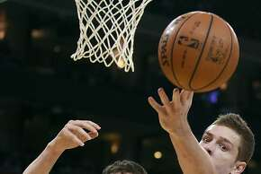 Golden State Warriors forward David Lee reaches for the ball in front of Minnesota Timberwolves forward Kevin Love (42) during the first quarter of an NBA basketball game in Oakland, Calif., Monday, March 19, 2012. (AP Photo/Jeff Chiu)