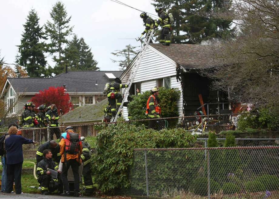 Firefighters work the scene of a house fire in the 11700 block of 22nd Avenue NE on Tuesday, November 5, 2013. Two people in their 80s were injured in the blaze. Photo: JOSHUA TRUJILLO, SEATTLEPI.COM / SEATTLEPI.COM