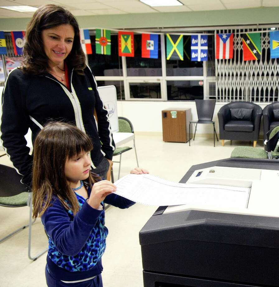 Dakota Price, 7, deposits a ballot for her mother, Jessica, at Neighbor's Link in Stamford, Conn., on Tuesday, November 5, 2013. Photo: Lindsay Perry / Stamford Advocate