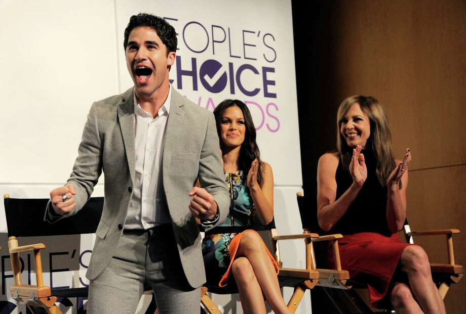 "Presenter Darren Criss, a cast member in the television series ""Glee,"" reacts to his nomination for Favorite Comedic TV Actor during nominations for the 40th Annual People's Choice Awards at The Paley Center for Media on Tuesday, Nov. 5, 2013 in Beverly Hills, Calif. Looking on are fellow presenters Rachel Bilson, center, and Allison Janney. The show will be held on Jan. 8, 2014 at the Nokia Theater L.A. Live in Los Angeles. (Photo by Chris Pizzello/Invision/AP) ORG XMIT: CACP101 Photo: Chris Pizzello / Invision"