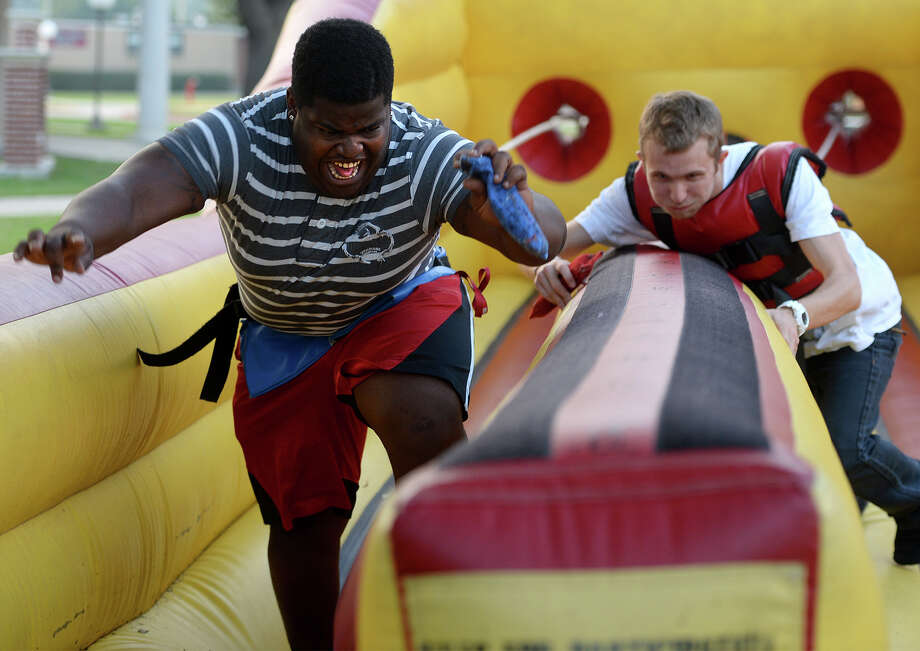 Max Jones, left, and Brenen Cox reach for the goal mark of a bungee race during the Presidents Outdoor Extravaganza at Lamar on Tuesday. The event was designed to generate excitement among students and as a lead up to Kenneth Evan's investitures on Thursday.  Photo taken Tuesday, November 05, 2013 Guiseppe Barranco/The Enterprise Photo: Guiseppe Barranco, Photo Editor