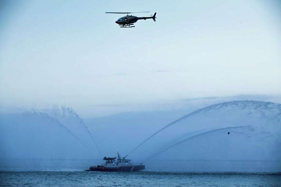 A helicopter circles overhead and a fireboat engages it's apparatus as the cruise ship Caribbean Princess leaves from the Bayport Cruise Terminal Nov. 5, 2013 in Pasadena, TX. Photo: Eric Kayne, For The Chornicle / Eric Kayne