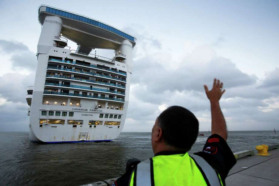 A officer waves as the cruise ship Caribbean Princess leaves from the Bayport Cruise Terminal Nov. 5, 2013 in Pasadena, TX. Photo: Eric Kayne, For The Chornicle / Eric Kayne