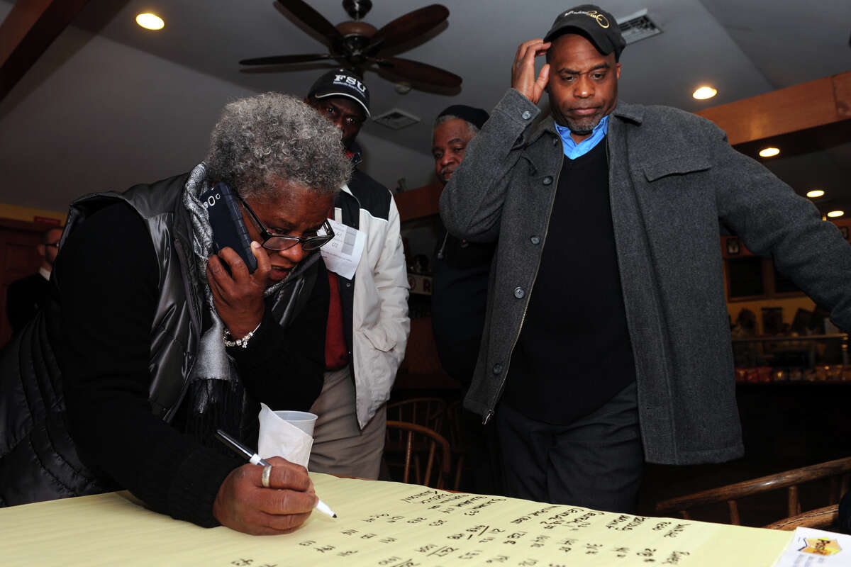 Democratic candidate Andre Baker watches as Marilyn Moore tallies election returns at the Red Rooster Deli, in Bridgeport, Conn., Nov. 5, 2013. Baker secured a seat on the Bridgeport Board of Education.