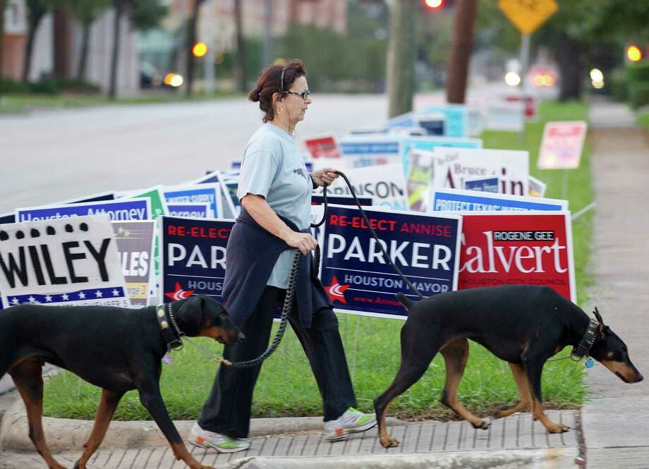 June Braden takes her dogs, Shaq, left, and Zino, on a walk past candidate signs outside the Metropolitan Multi-Service Center before voting started on election day Tuesday, Nov. 5, 2013, in Houston. Photo: Johnny Hanson, Houston Chronicle / Houston Chronicle
