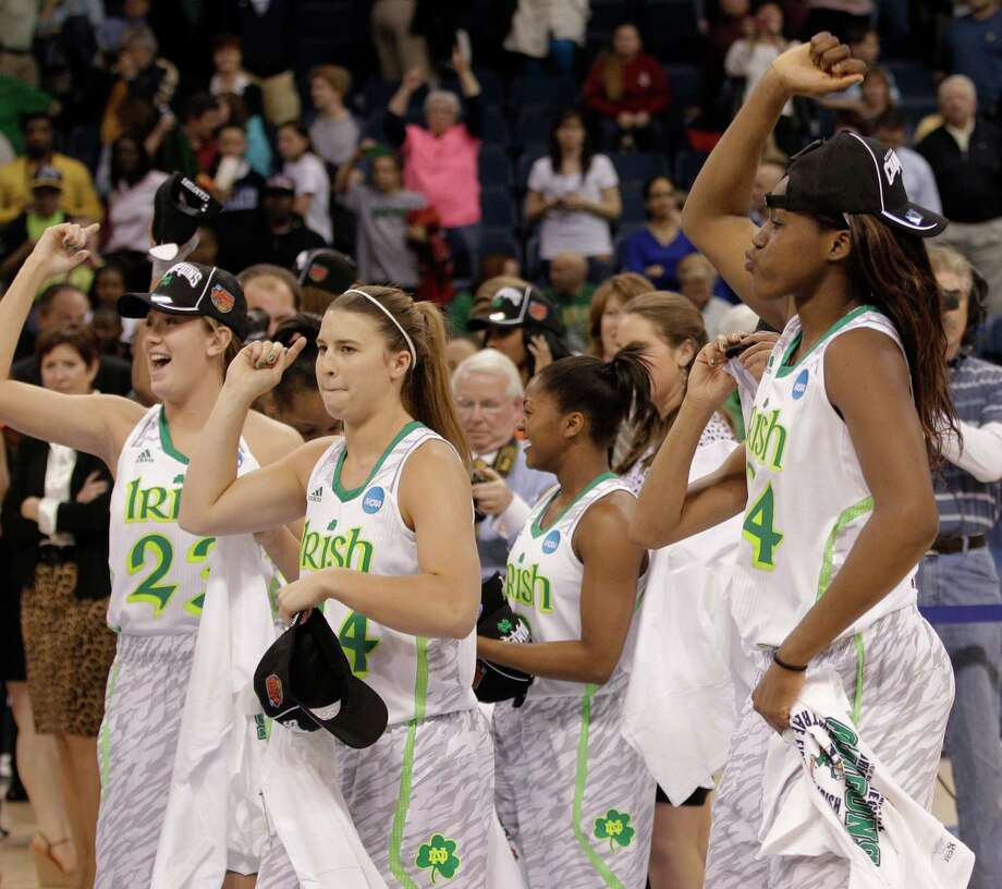 FILE - In this April 2, 2013 file photo, Notre Dame players celebrate an 87-76 win over Duke at the regional final of the NCAA women's college basketball tournament in Norfolk, Va. Notre Dame has been to three straight Final Fours as it enters the Atlantic Coast Conference. The Fighting Irish are determined to start their ACC tenure by dethroning Duke, who has won three of the past four league titles. (AP Photo/Steve Helber, File) ORG XMIT: NY150 Photo: Steve Helber / AP