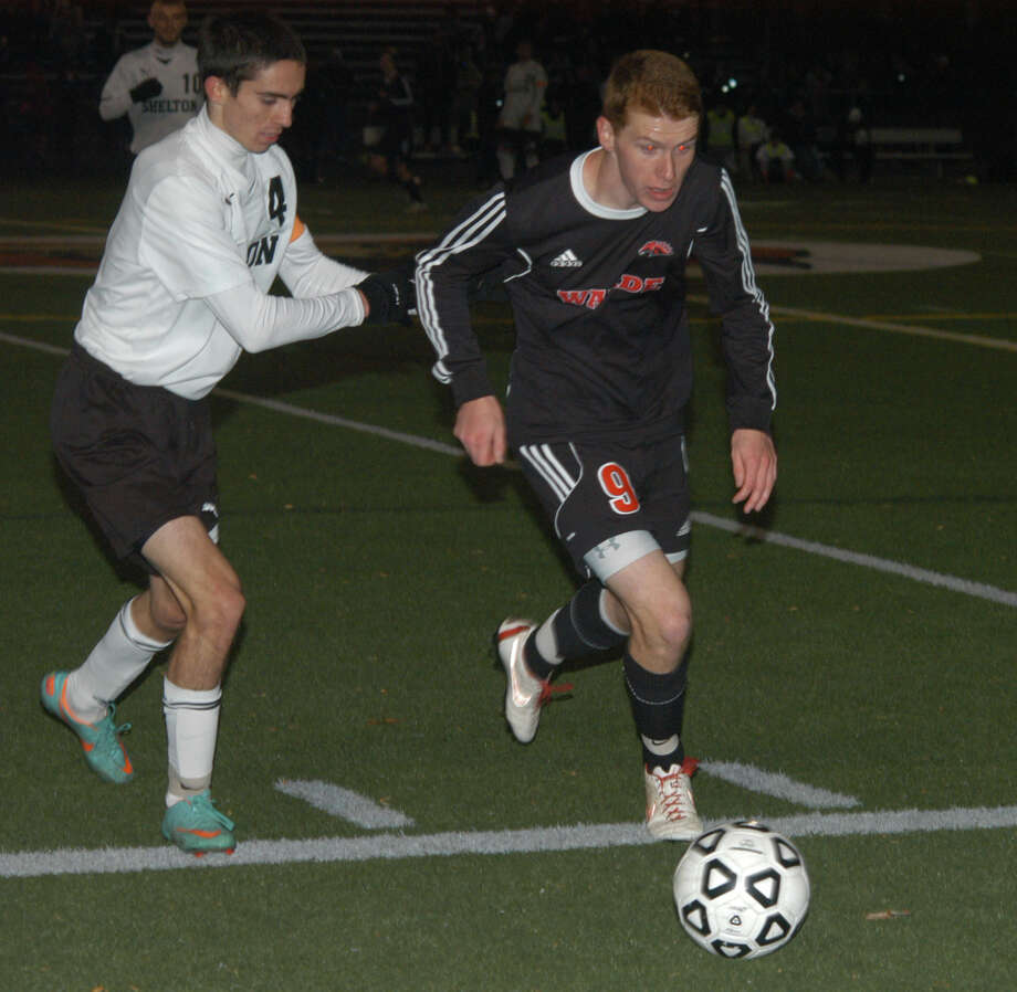 Shelton's John Hunter (4) chases Fairfield Warde's Peter Stymacks (9) on Tuesday, Nov. 5 in the Mustangs' 1-0 win at Shelton in a CIAC Class LL boys soccer state tournament first-round match. Photo: Andy Hutchison / Fairfield Citizen